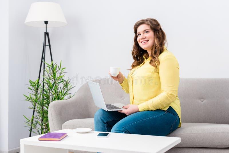 mujer sonriente joven con la taza de café y de ordenador portátil que se sientan en el sofá foto de archivo