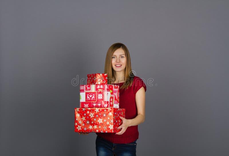 Mujer sonriente joven con los regalos de Navidad imagenes de archivo