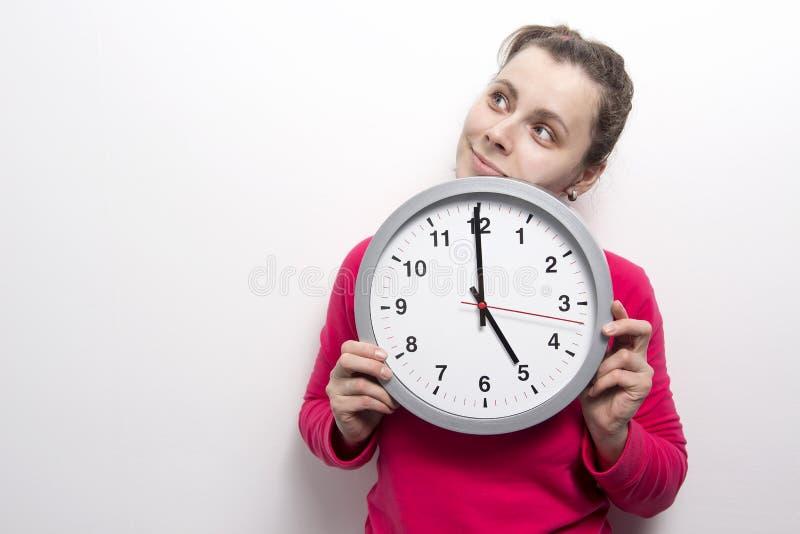 Mujer sonriente joven con mirada clásica del reloj en el lado Concepto de la mujer del tiempo Los controles morenos de la muchach imágenes de archivo libres de regalías