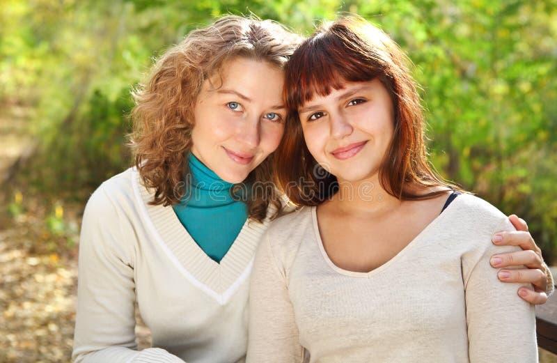 Mujer sonriente joven con su hija adolescente fotos de archivo libres de regalías