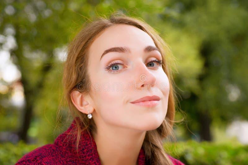 Mujer sonriente joven contra follaje verde imagen de archivo