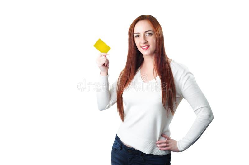 Mujer sonriente joven del pelirrojo que sostiene la tarjeta de crédito del oro imagenes de archivo