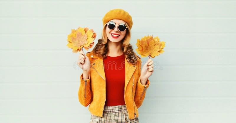 Mujer sonriente joven del retrato caliente del otoño con las hojas de arce amarillas en boina francesa sobre la pared gris foto de archivo