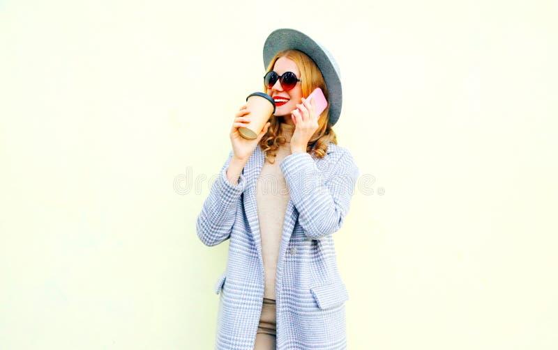 Mujer sonriente joven elegante del retrato que invita a smartphone en la calle de la ciudad, chaqueta de la capa que lleva, sombr fotografía de archivo