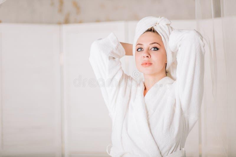 Mujer sonriente joven en albornoz con la toalla en la cabeza imagen de archivo libre de regalías