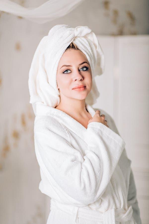 Mujer sonriente joven en albornoz con la toalla en la cabeza fotos de archivo