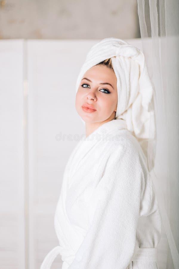 Mujer sonriente joven en albornoz con la toalla en la cabeza fotos de archivo libres de regalías