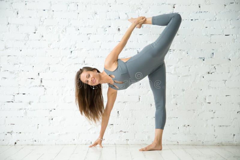 Mujer sonriente joven en ejercicio de la media luna, estudio blanco foto de archivo libre de regalías
