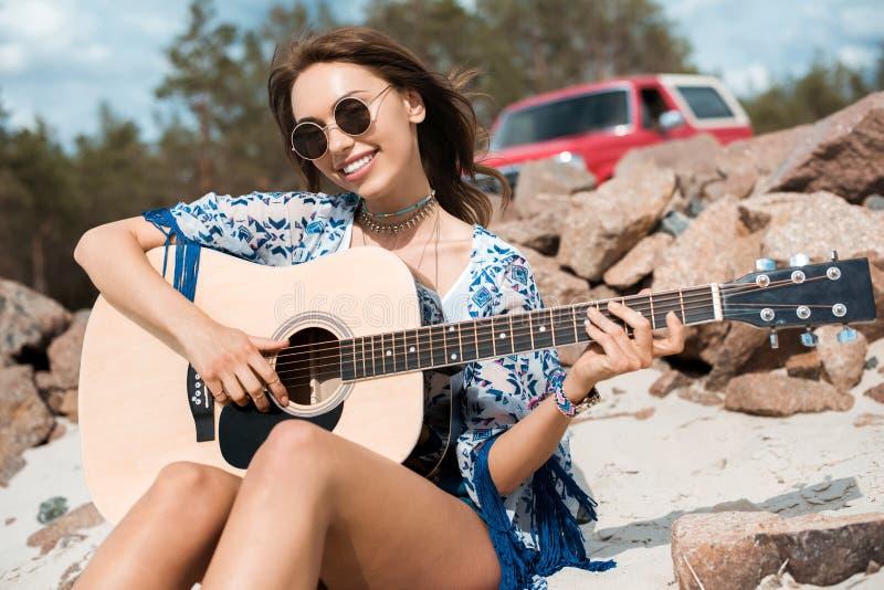mujer sonriente joven en jugar de las gafas de sol acústico fotos de archivo