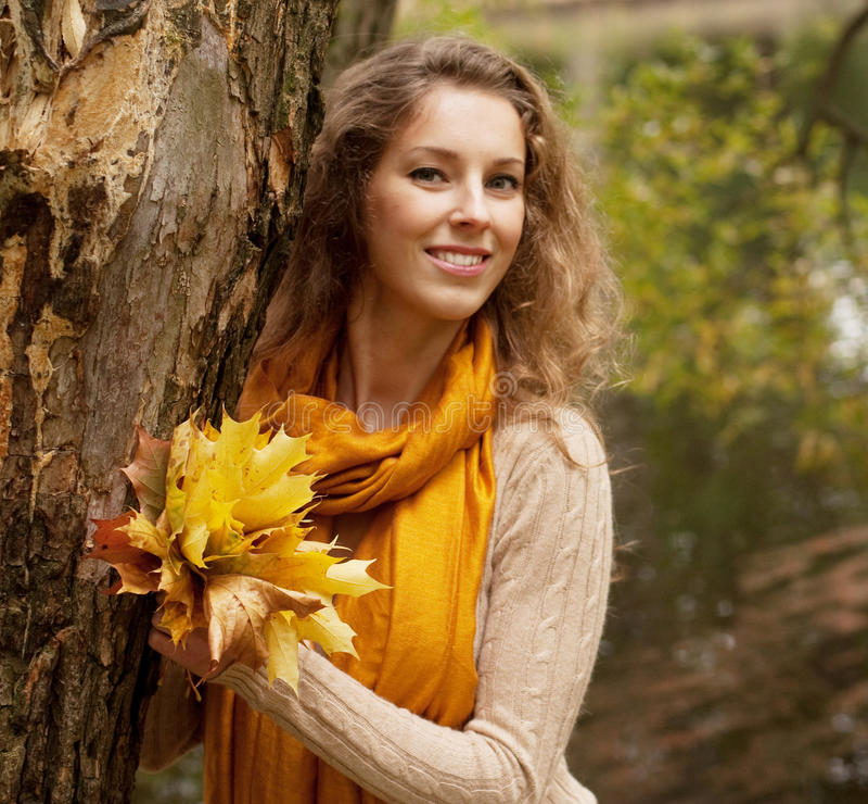 Mujer sonriente joven en parque del otoño imagen de archivo libre de regalías