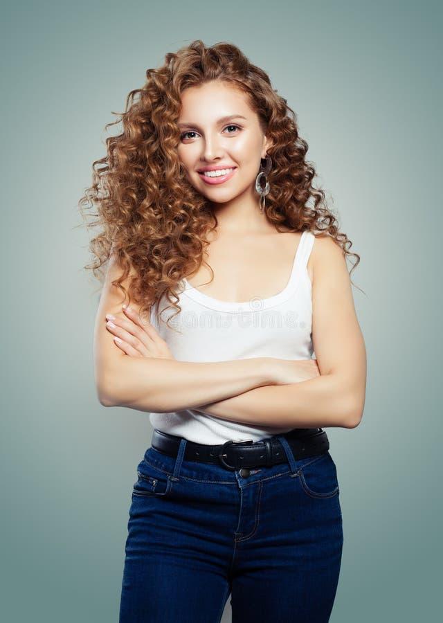 Mujer sonriente joven en tejanos Muchacha linda con el pelo rubio fotografía de archivo libre de regalías