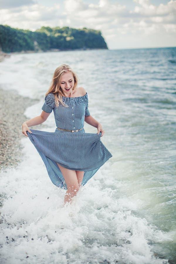 Mujer sonriente joven en un vestido largo imagenes de archivo