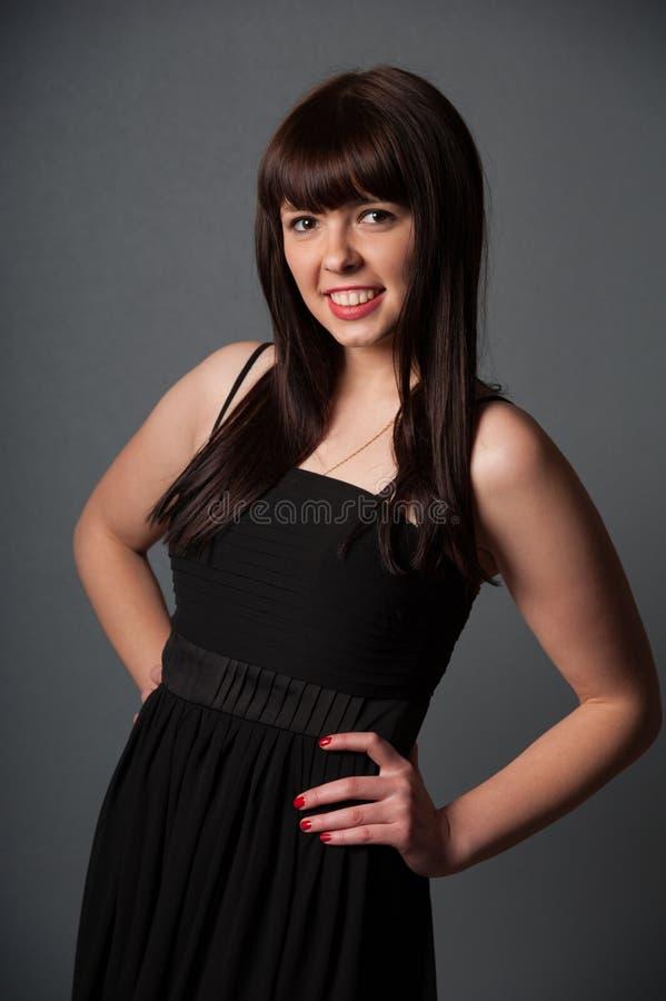 Mujer sonriente joven en vestido negro fotos de archivo