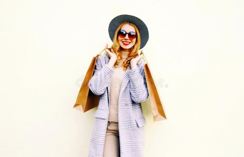 Mujer sonriente joven feliz con los bolsos de compras en la capa rosada, sombrero redondo foto de archivo libre de regalías
