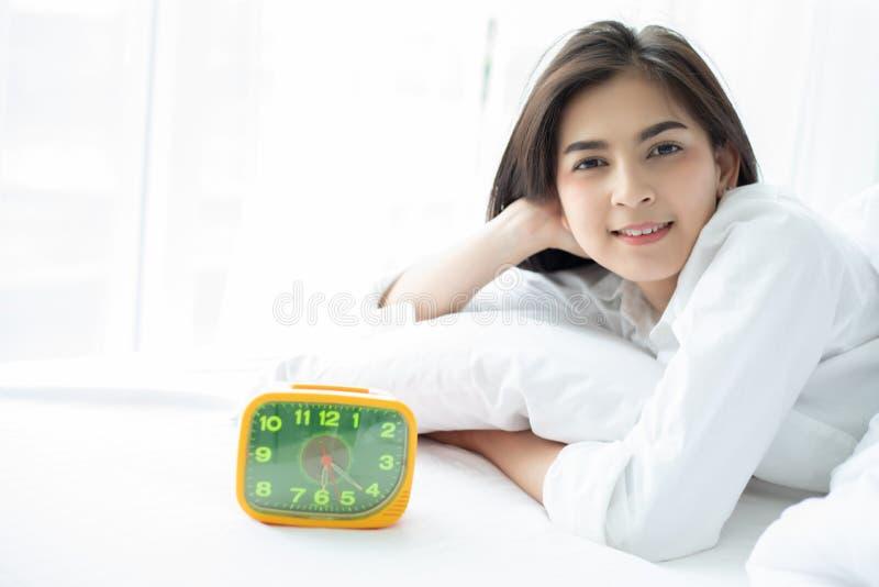 Mujer sonriente joven hermosa de la mujer asi?tica que se sienta en cama y que estira por la ma?ana en el dormitorio despu?s de d fotografía de archivo