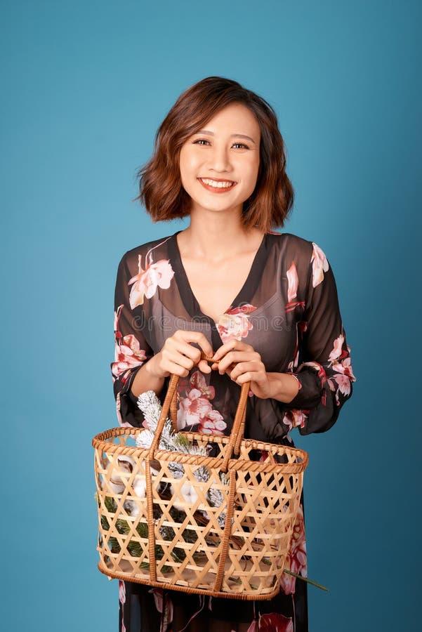 Mujer sonriente joven hermosa en el vestido del vintage que sostiene una cesta con las flores Chica joven bonita del retrato del  imagenes de archivo