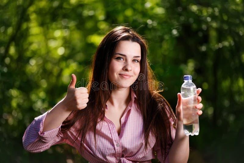 Mujer sonriente joven hermosa feliz que sostiene una botella de wa limpio fotos de archivo