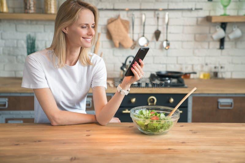 Mujer sonriente joven hermosa que charla en el teléfono mientras que hace la ensalada en la cocina Alimento sano Ensalada vegetal fotos de archivo