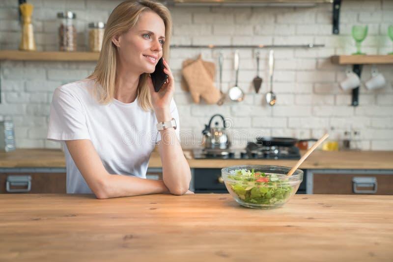 Mujer sonriente joven hermosa que habla en el teléfono mientras que hace la ensalada en la cocina Alimento sano Ensalada vegetal  imagen de archivo