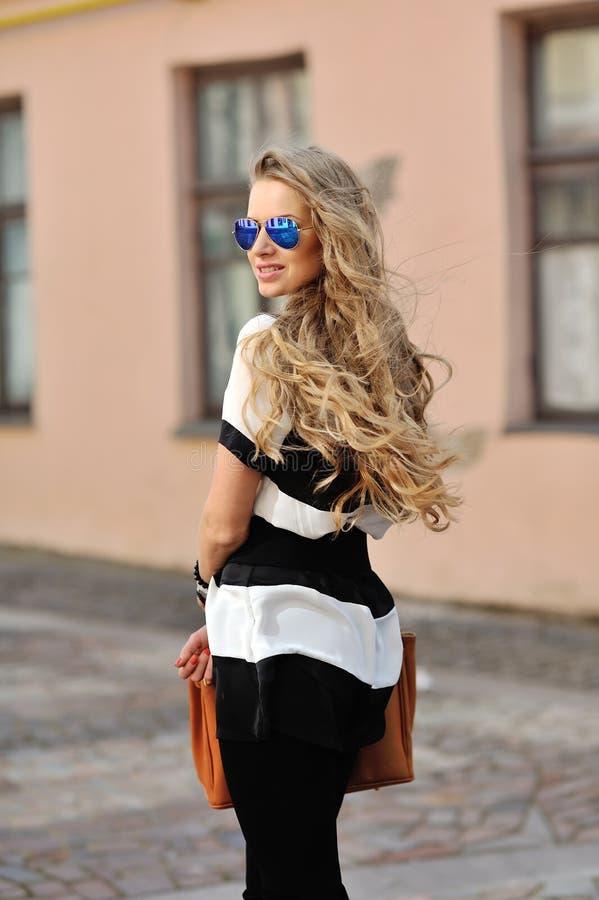 Mujer sonriente joven hermosa que presenta en gafas de sol foto de archivo libre de regalías