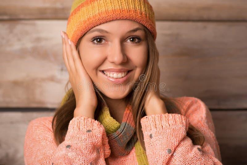 Mujer sonriente joven hermosa sobre fondo de madera y x28; winter& x29; foto de archivo