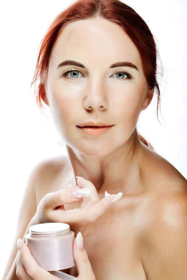 Mujer sonriente joven que aplica la crema en su cara imágenes de archivo libres de regalías