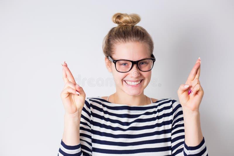 Mujer sonriente joven que cruza sus fingeres y esperanzas de la suerte, éxito Vidrios que llevan de la muchacha rubia hermosa y v imágenes de archivo libres de regalías
