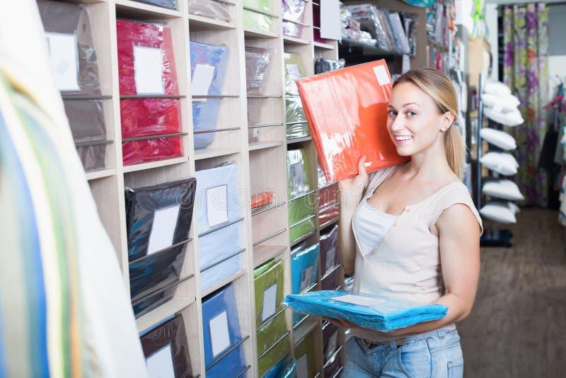 Mujer sonriente joven que elige el sistema del lecho de la tela foto de archivo libre de regalías