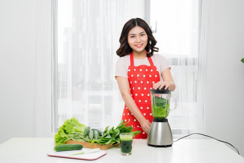 Mujer sonriente joven que hace el smoothie con verdes frescos en el ble fotos de archivo libres de regalías