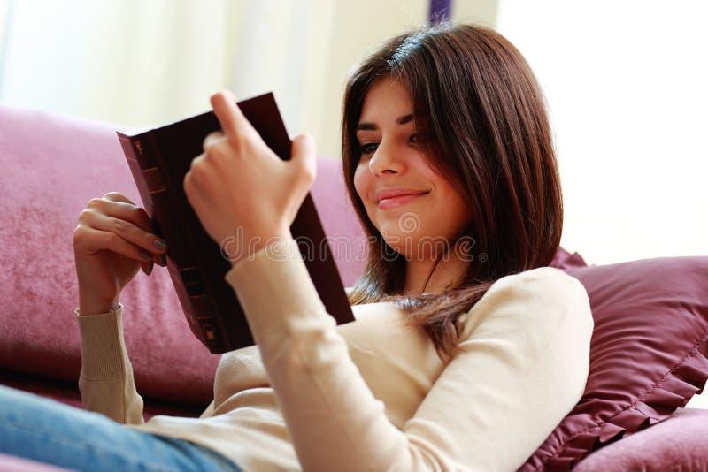 Mujer sonriente joven que miente en el sofá y el libro de lectura fotos de archivo
