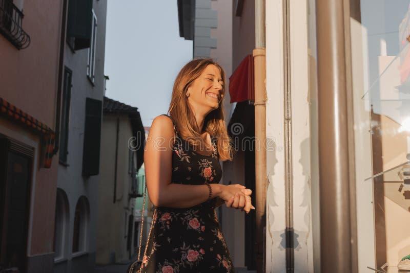Mujer sonriente joven que mira la ventana de la tienda en un callejón en ascona fotografía de archivo libre de regalías