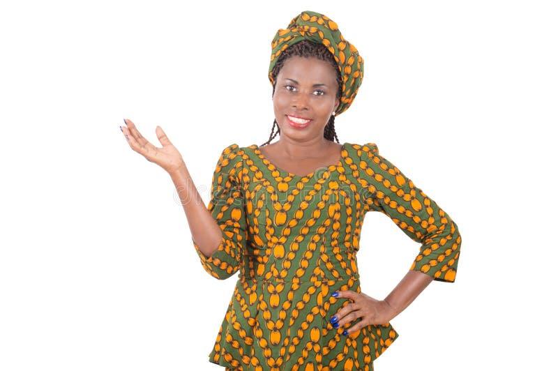 Mujer sonriente joven que muestra el espacio de la copia en el fondo blanco fotografía de archivo libre de regalías