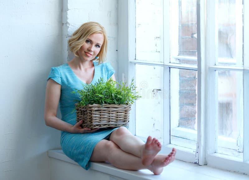Mujer sonriente joven que se sienta en alféizar con la caja con las plantas imagen de archivo libre de regalías
