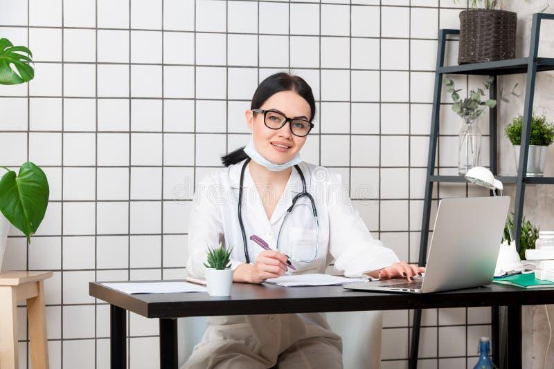 Mujer sonriente joven que se sienta en el escritorio, trabajando en el ordenador con los documentos médicos en oficina ligera en  fotos de archivo libres de regalías