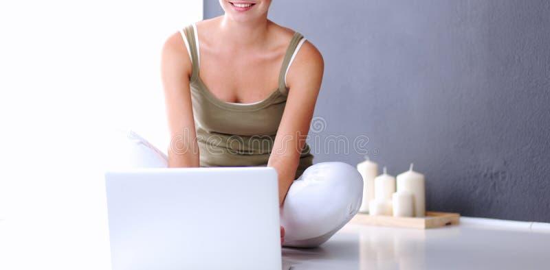 Mujer sonriente joven que se sienta en el piso con el ordenador portátil cerca de la pared gris imagen de archivo
