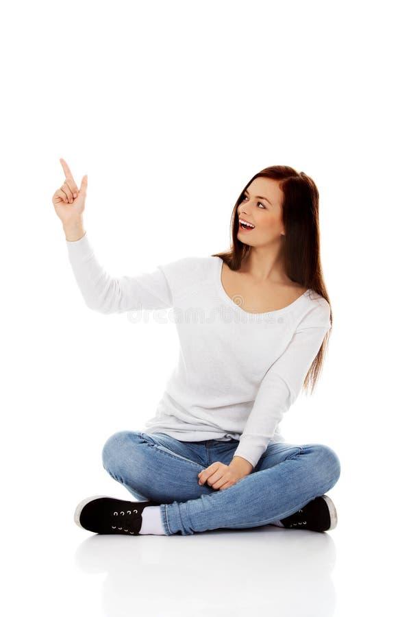 Mujer sonriente joven que se sienta en el piso y que destaca fotografía de archivo libre de regalías