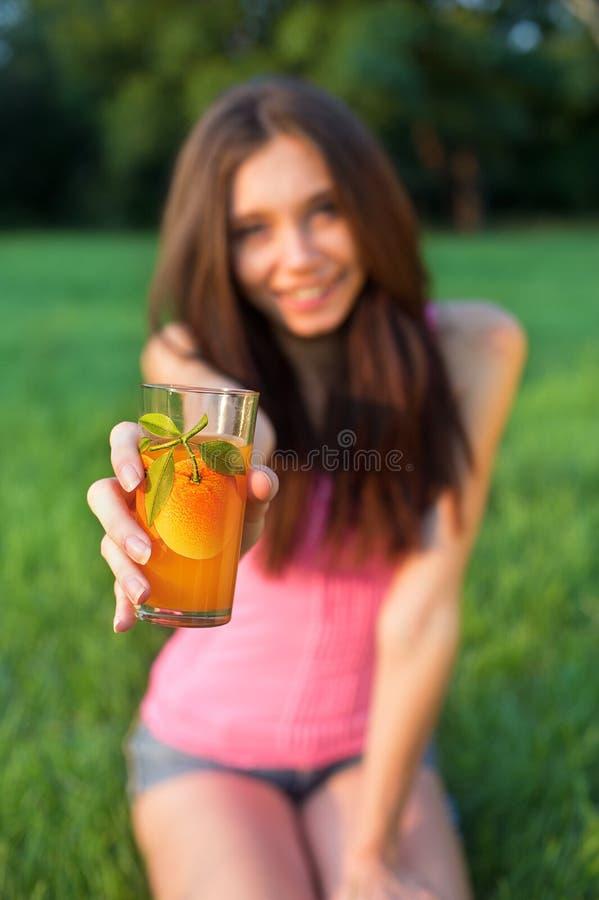 Mujer sonriente joven que se sienta en la hierba con el vidrio de ju anaranjado foto de archivo libre de regalías