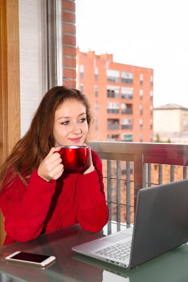 Mujer sonriente joven que se sienta en la tabla con la taza de café, de ordenador portátil y de smartphone imagenes de archivo