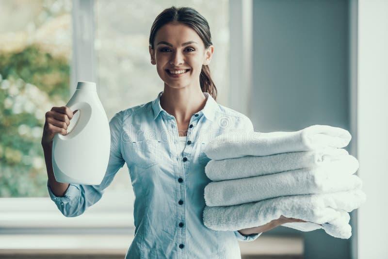 Mujer sonriente joven que sostiene el detergente para ropa imagen de archivo