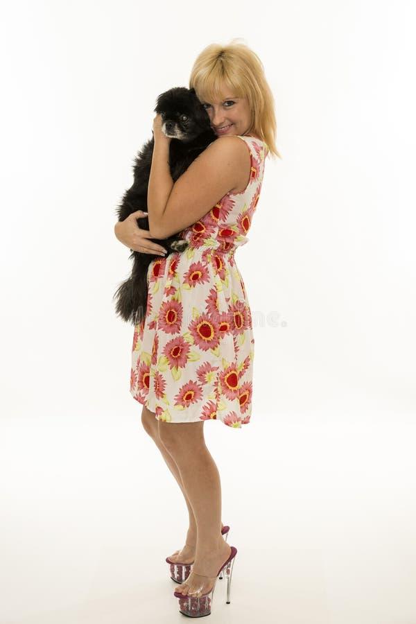 Mujer sonriente joven que sostiene en estos brazos un perro fotos de archivo libres de regalías
