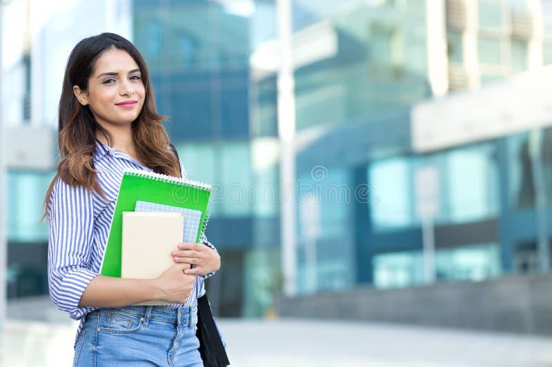 Mujer sonriente joven que sostiene los libros, estudio, educación, conocimiento, concepto de la meta imágenes de archivo libres de regalías