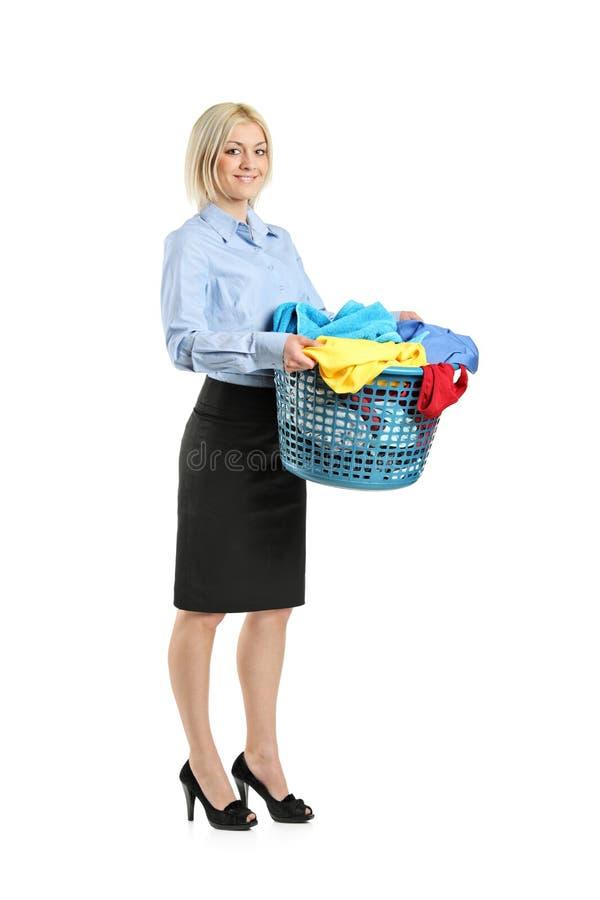 Mujer sonriente joven que sostiene una cesta de lavadero foto de archivo