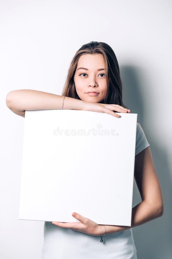 Mujer sonriente joven que sostiene una hoja de papel en blanco fotografía de archivo libre de regalías