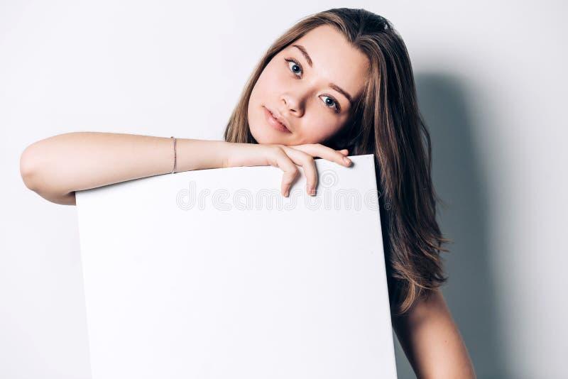 Mujer sonriente joven que sostiene una hoja de papel en blanco para hacer publicidad, foto de archivo libre de regalías