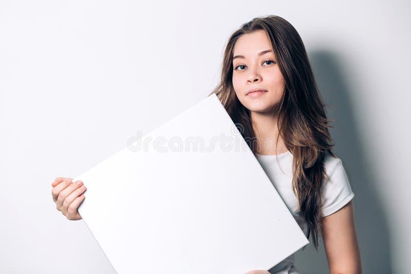 Mujer sonriente joven que sostiene una hoja de papel en blanco para hacer publicidad imagen de archivo libre de regalías