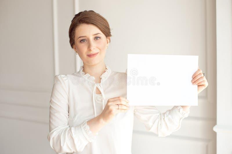 Mujer sonriente joven que sostiene una hoja de papel en blanco para hacer publicidad Muchacha que muestra la bandera con el espac imágenes de archivo libres de regalías