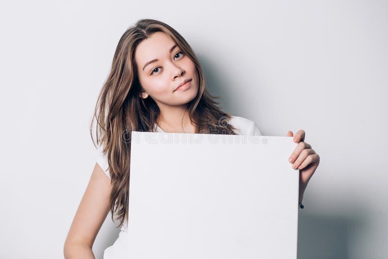 Mujer sonriente joven que sostiene una hoja de papel en blanco para hacer publicidad, primer fotografía de archivo