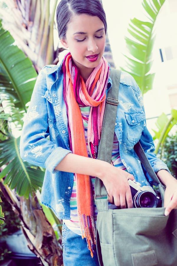Mujer sonriente joven que toma la cámara hacia fuera de su bolso afuera imagenes de archivo