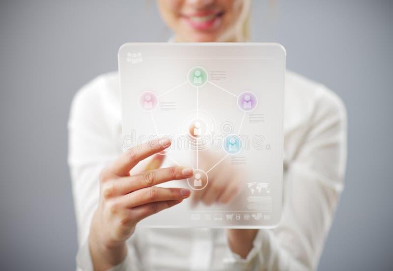 Mujer sonriente joven que usa el ordenador de la tablilla imágenes de archivo libres de regalías