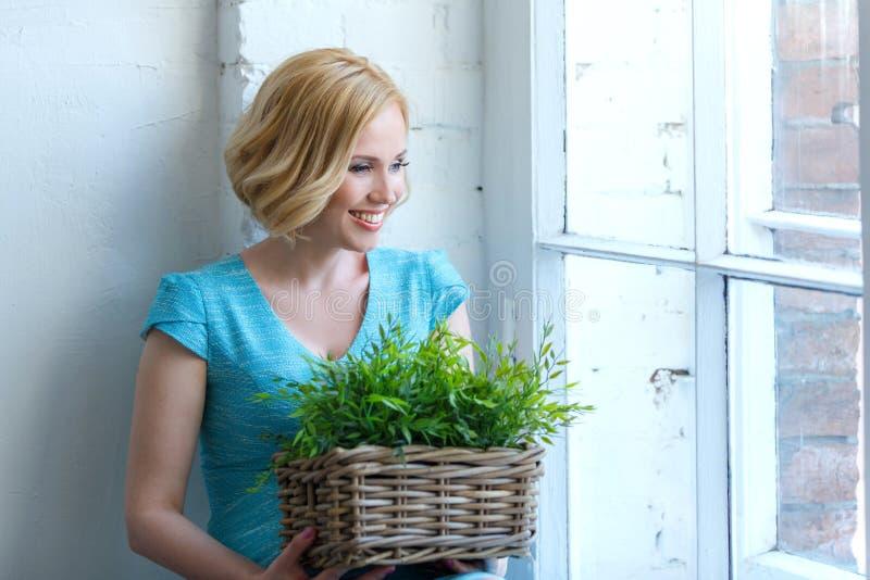 Mujer sonriente linda con la cesta con la mirada de las plantas verdes imagen de archivo